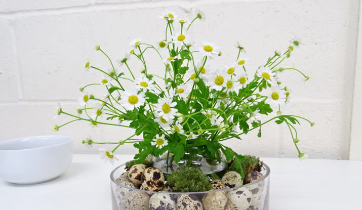 Now, you can start creating the arrangement in the centre. Start by placing the 'intermediate' flowers, the Tanacetum and Forget Me Not's (Myosotis) into the vase to create a frame for the next step.