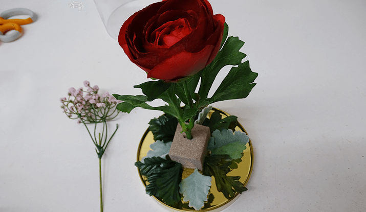 Add the focal flowers to the arrangement. Due to the height of the cloche, you will need to take this into consideration when creating the arrangement.