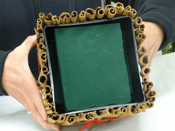 Measure the container and add a piece of soaked floral foam to the container as shown in the photograph.