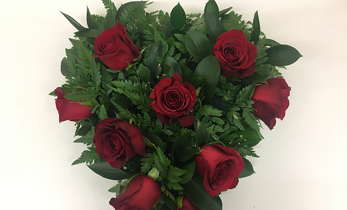 Start to arrange the roses or chosen focal flower into your arrangement. Depending on your personal preference, you can either make a contemporary design with grouped flowers or a more traditional design with evenly balanced flowers.