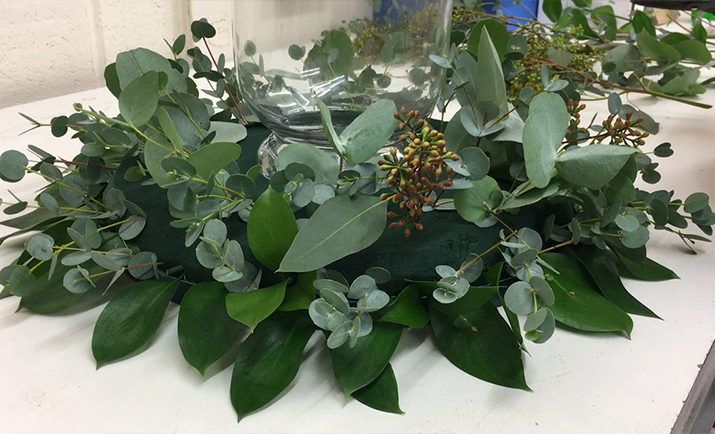 Continue to fill in the base of the arrangement with your foliage of choice. Here we are using a combination of Eucalyptus to add texture and interest to the arrangement. Cut the foliage into shorter stems and place into the floral foam posy pad.