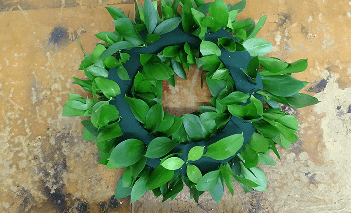 Continue to fill in the base with your chosen foliage. Here, we are only using the Hard Ruscus as the foliage, but you can use other types i.e Eucalyptus, Salal, Dusty Miller etc. for added texture and interest.
