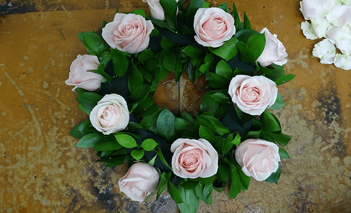 Add your focal flowers into the arrangement. Here, we are using Rose Sweet Avalanche. Before placing the stems into the arrangement, cut the stems short and remove the guard petals (optional).