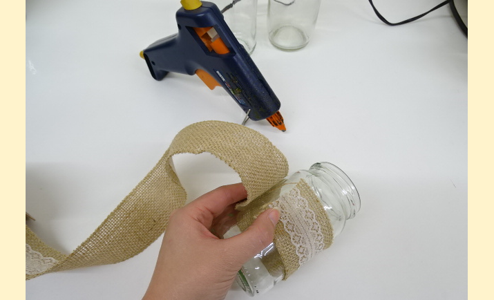 Depending on the size of the jam jars or bottles you are decorating, it is a good idea to measure the diameter of each jar with the ribbon to ensure you do not waste your materials. As seen in the photograph, with the ribbon you need to make sure there is an overlap to allow enough space to glue and link one side to the other.