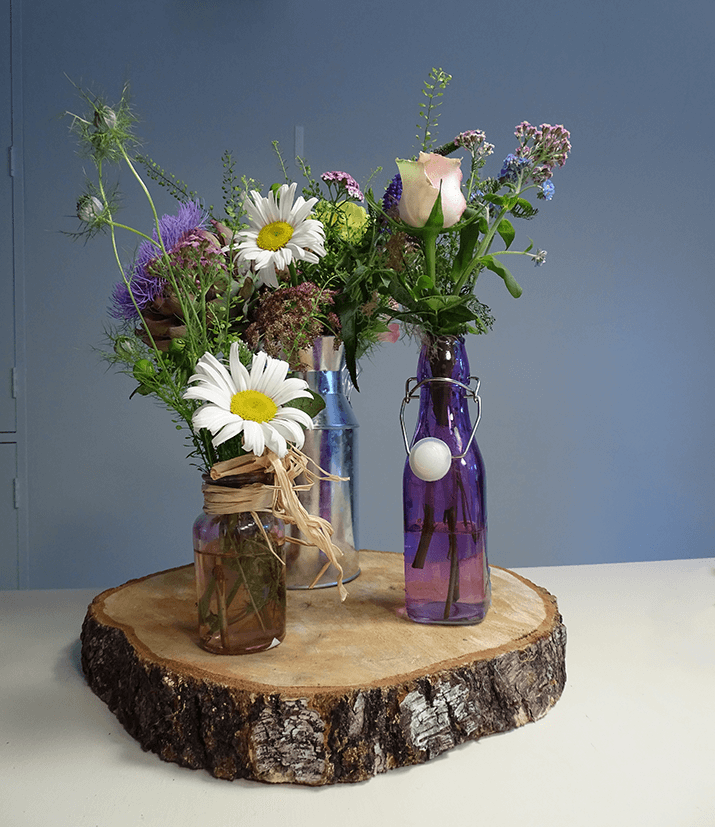 Depending on the type of jam jars or bottles you are using, position them on a wood slice or book and cluster in 3 to 5 vases varying the height to add interest to the design.